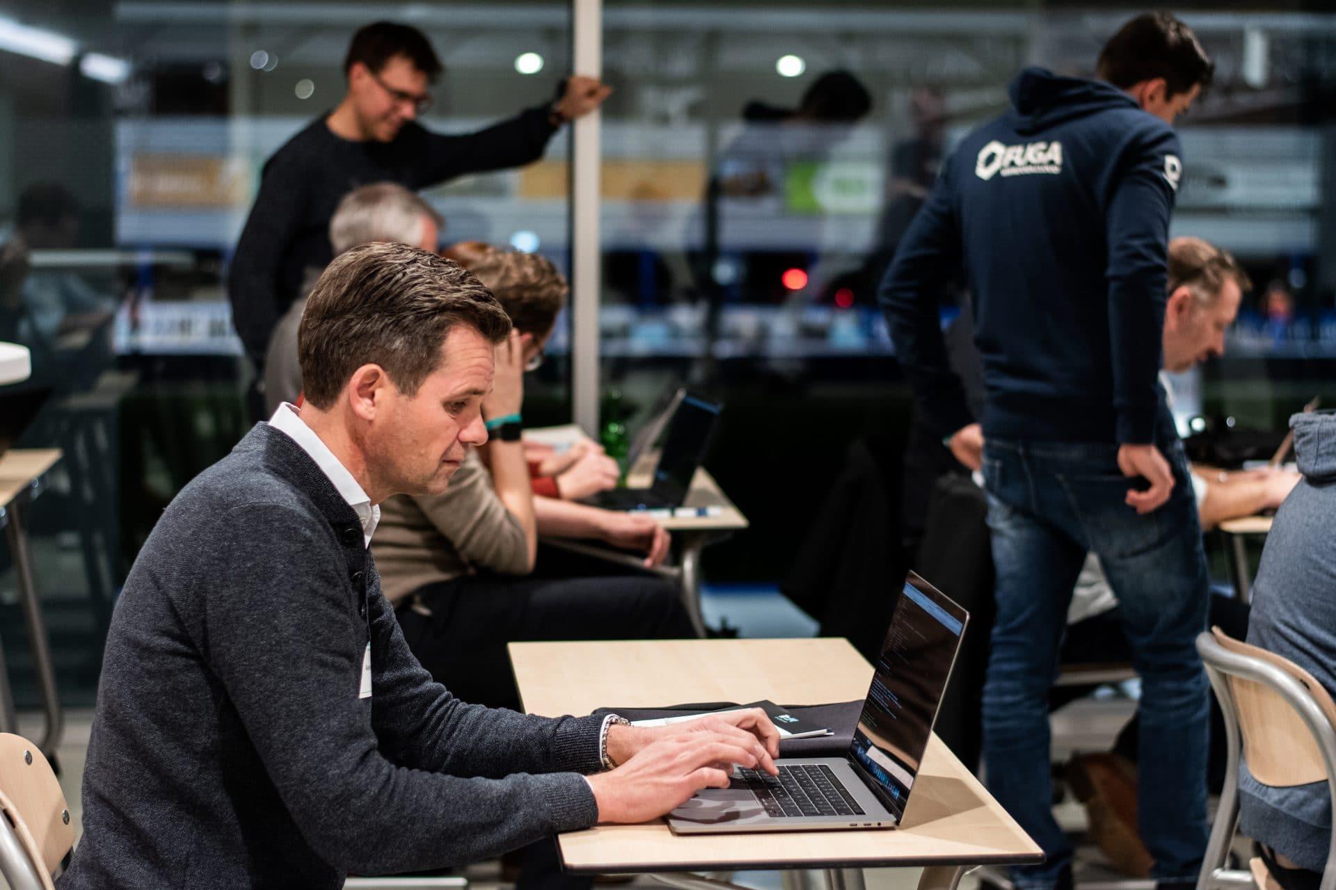 deelnemers achter laptop tijdens workshop